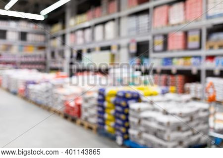 Blurred Background Of A Hardware Store With Bags Of Cement.