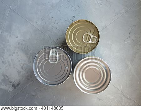 Various Canned Foods In Tin Cans On Concrete Grey Background. Non-perishable, Long Shelf Life Food F