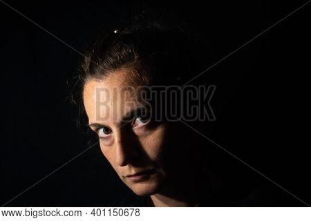 Dark Profile Portrait Of A Very Dimly Lit Woman. The Woman Is Looking Straight Ahead, Conveying A Fe