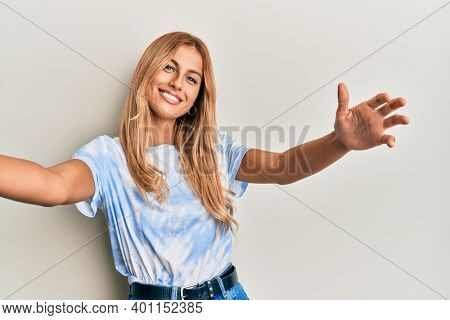 Beautiful blonde young woman wearing tye die tshirt looking at the camera smiling with open arms for hug. cheerful expression embracing happiness.