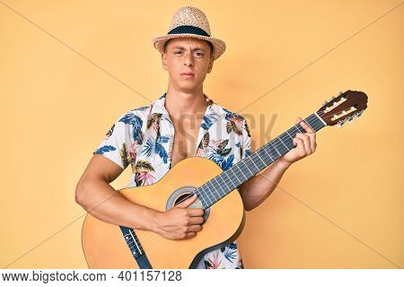 Young hispanic boy wearing summer style playing classical guitar skeptic and nervous, frowning upset because of problem. negative person.