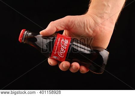 Lviv, Ukraine - December 15, 2020: Coca Cola Bottle With A Drink In Hand Black Background