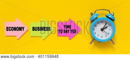 Finance And Economics Concept. On A Yellow Background, A Blue Alarm Clock, And Paper Arrows. On The