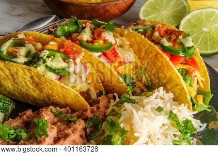 Mexican Beef Tacos With Rice Refried Beans Tortilla Chips And Various Toppings