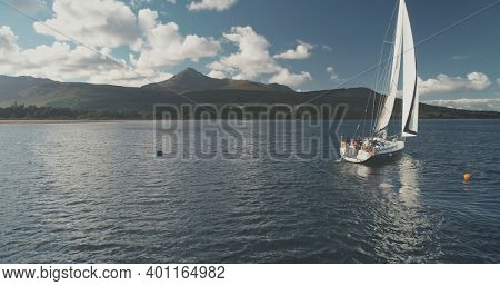 Yacht racing at ocean bay coast aerial. Passengers on sailboat at open sea at summer cloudy day. Brodick harbor at mountain island of Arran, Scotland. Cinematic scenery of luxury cruise on sail boat.