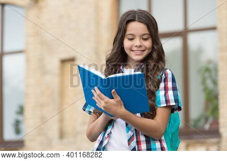 Happy Kid With Long Wavy Hair In Casual Style Read School Book In Schoolyard, Reading.