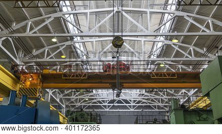 Yellow Overhead Crane With Linear Traverse And Hooks In Engineering Plant Shop.