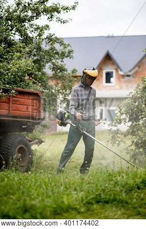 Worker With A Gas Mower In His Hands, Mowing Grass In Front Of The House. Trimmer In The Hands Of A