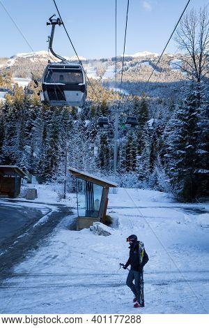 Whistler, Bc, Canada - Dec 27, 2020: Blackcomb Gondola With Skiier Walking In Front.