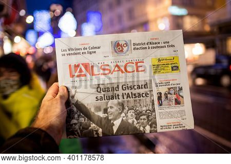Strasbourg, France - Dec 4, 2020: Man Holding Lalsace French Newspaper At Press Kiosk Announcing The