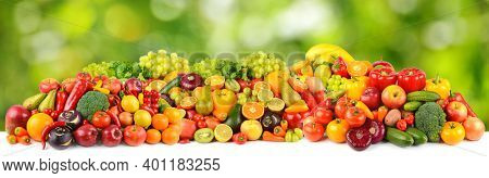 Wide pattern of ripe and fresh fruits and vegetables on green natural background.