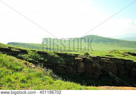 A Rocky Top Of A High Hill Overlooking A Fertile Valley On A Sunny Summer Day.