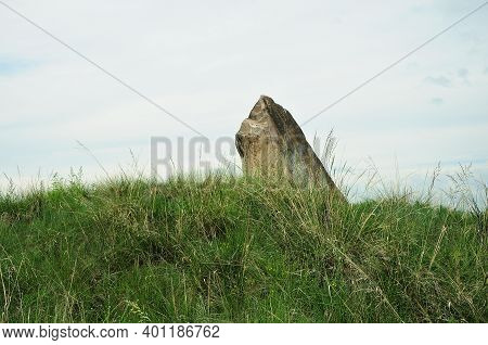 An Ancient Burial Stone Stands From The Steppe Overgrown With Tall Grass.