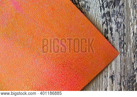 Embossed Orange Paper With  Holography And Serigraphy  Effect On Wooden Background