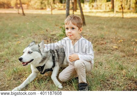 Child Camping With Pet Dog. Beautiful Young Boy Hugging His Puppy In Summer Park. Little Boy Playing