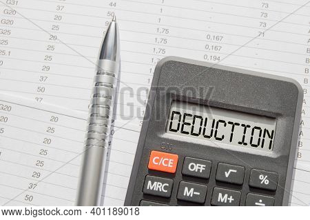 The Word Deduction Is Written On The Digital Display Of The Calculator Lying On The Financial Statem