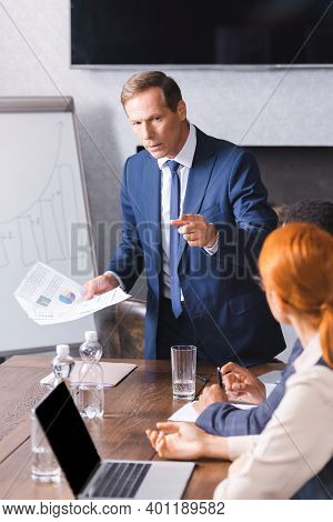 Serious Executive With Papers Pointing With Finger At Businesswoman Near African American Colleague