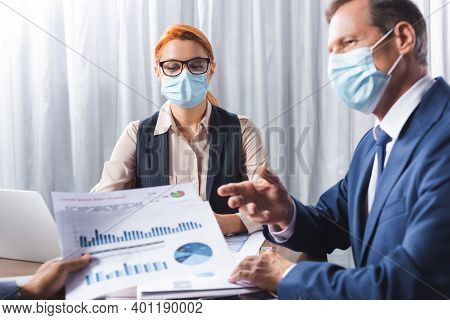 Businessman In Medical Mask Gesturing And Looking At Colleague With Papers On Blurred Foreground In