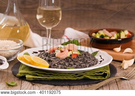 Squid Ink Risotto With Vegetables On White Dish.