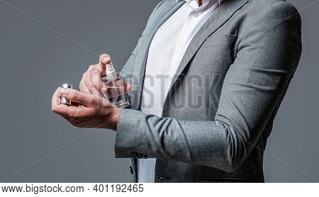 Man Holding Up Bottle Of Perfume. Men Perfume In The Hand On Suit Background. Handsome Man In Formal