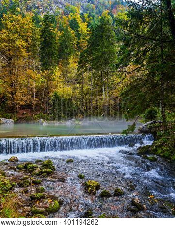 Travel to Slovenia. Cloudy foggy autumn day. Julian Alps. A picturesque shallow lake with glacial greenish water. A light fog rises above the water. Artificial waterfall - dam