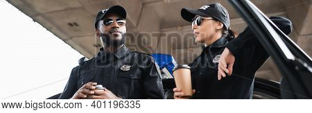 Multicultural Police Officers With Paper Cups Talking While Leaning On Patrol Car On Blurred Backgro
