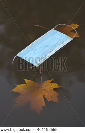 Discarded Medical Mask For Viral Infections, Floats In An Autumn Puddle