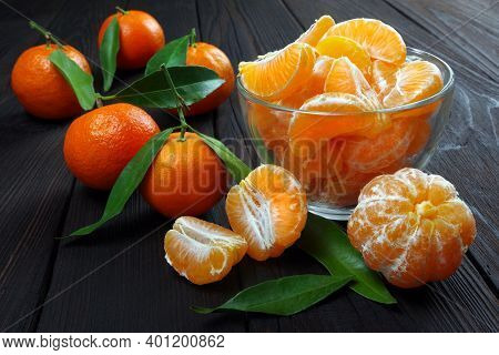 Ripe Tangerines On A Wooden Table Close Up. Slices Of Tangerine