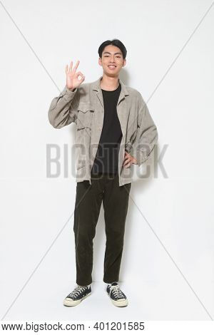 full length  young man in gray shirt ,black shirt and black jeans,and sneakers with okay hand sign