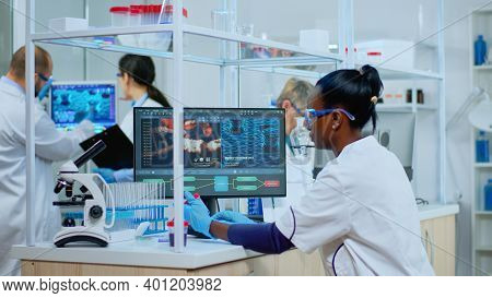 Black Woman Researcher Carrying Out Scientific Research In Equipped Lab. Multiethnic Team Examining