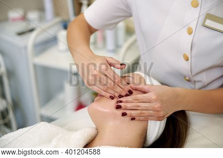 Cosmetician Making Facial Lifting Massage For Pretty Young Woman In Spa Salon