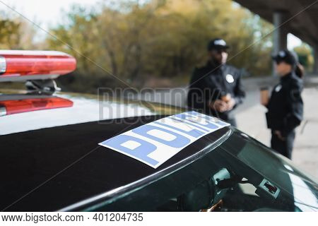 Auto With Police Lettering Near Multicultural Police Officers On Blurred Background Outdoors.