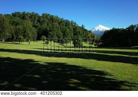 Nature of Chile. Beautiful landscape, sun and shadow, Green grass meadow and forest on hill, Snowy cone of Villarrica volcano under blue sky in sunny day. Green environment, Pucon