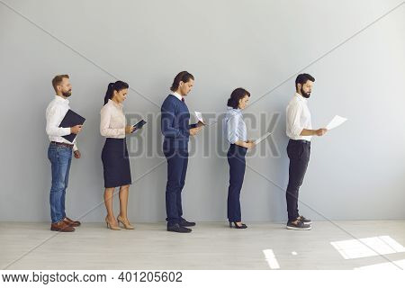Job Seekers Applicants For Vacancy Standing In Line With Resumes And Waiting For Interview