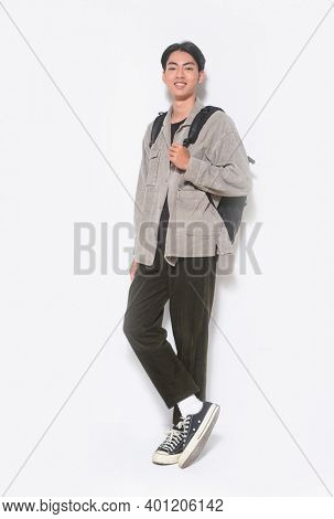 full length  young man in gray shirt ,black shirt and black jeans,and sneakers with backpack in studio