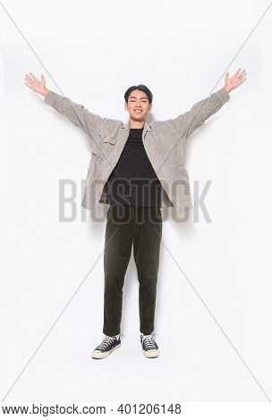 full length  young man in gray shirt ,black shirt and black jeans,and sneakers and raised up arms posing in studio