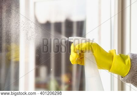 Cleaning A Window With Spray Detergent, Yellow Rubber Gloves And Dish Cloth On Work Surface Concept