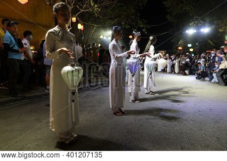 Hoi An, Vietnam, December 28, 2020: Girls Dressed In White With The Characteristic Lanterns In Hand