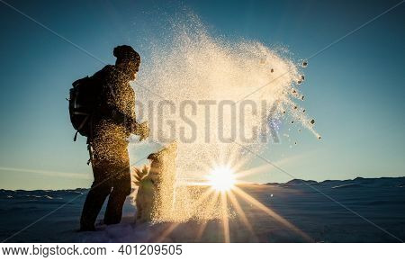 man and dog having fun in fresh snow