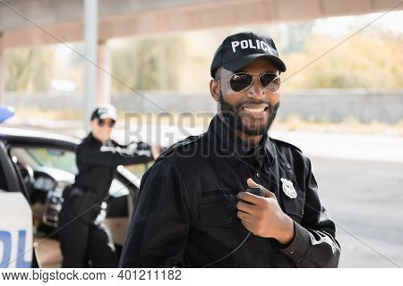 Happy African American Police Officer Looking At Camera While Holding Radio Set On Blurred Backgroun