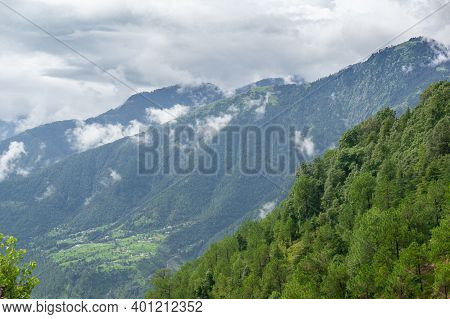 Landscape Shot Of Tree Covered Mountains In The Foreground With Cloud Covered Mountain Ranges In The