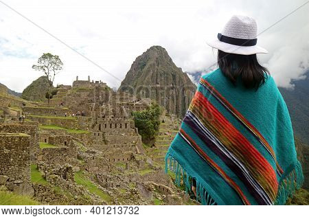 Female Traveler Looking At The Ancient Citadel Of Machu Picchu, Unesco World Heritage Site In Cusco