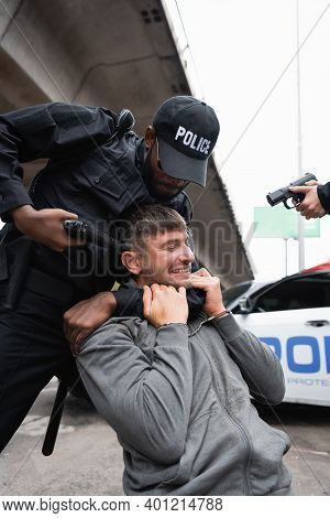 African American Policeman Choking Handcuffed Offender While Aiming With Pistol Near Colleague On Bl
