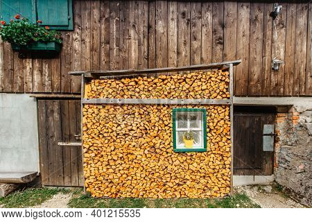 Mountain Hut With Stacked Firewood. Wall Of Firewood.background Of Dry Chopped Firewood In Cottage.w