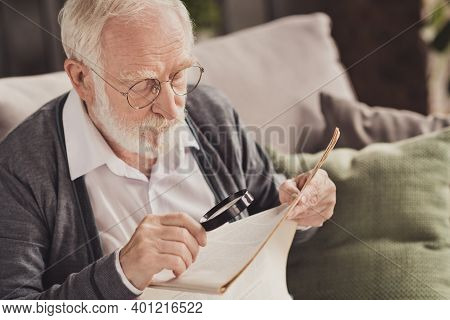 Photo Of Handsome Pensioner Wear Grey Cardigan Glasses Sitting Couch Reading Newspaper Holding Loupe