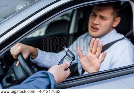 Policeman Giving Breathalyzer To Drunk Driver Showing Refuse Gesture, Blurred Background.