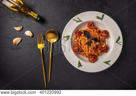 Pasta With Cherry Tomatoes, Cheese And Basil Served On Plate With Spoon, Fork And Olive Oil On Dark