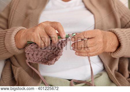 Elderly Woman Crocheting At Home, Closeup. Creative Hobby