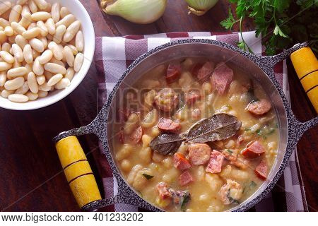 Stew Or White Bean Soup With Sausage, Vegetables, Spices And Herbs Served In Rustic Pan On Wooden Ta