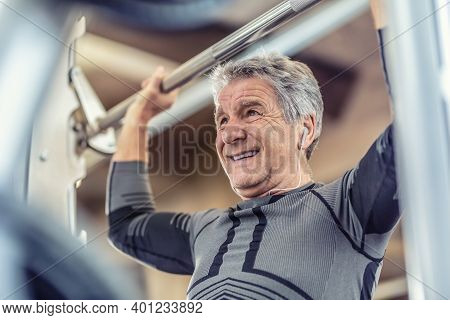 Exercising Shoulders Strength By An Older Man On A Fitness Machine Inside The Gym.